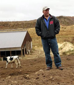 Wisconsin dairy farmer with barn and sand mine in background